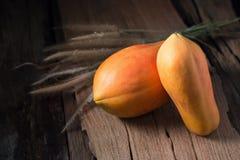 Papaye sur le fond en bois Découpé en tranches de la papaye Photos libres de droits