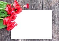 Εξασθενισμένες κόκκινες τουλίπες στο δρύινο καφετή πίνακα με το άσπρο φύλλο του pape Στοκ Εικόνα