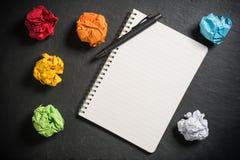 Papel amarrotado e e um caderno com uma página vazia Foto de Stock