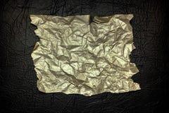 Papel arrugado del color oro con los bordes desiguales desiguales en un fondo de textura negro Fotografía de archivo