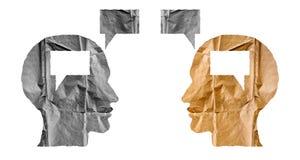 Papel arrugado formado como cabezas humanas y globos de la charla en pizca Imagen de archivo