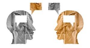 Papel arrugado formado como cabezas humanas y globos de la charla en pizca Foto de archivo