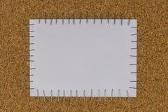 Papel atado en el tablero marrón por la grapadora Foto de archivo libre de regalías