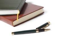 Papel blanco del cuaderno marrón y negro con la pluma en el fondo blanco Fotos de archivo