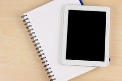 Papel branco do dispositivo eletrónico e do caderno na mesa de trabalho Imagens de Stock Royalty Free