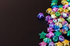 Papel colorido da estrela no fundo preto Foto de Stock
