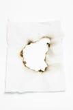 Papel con el agujero quemado fotos de archivo