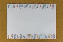 Papel con el clip de papel atado en el tablero marrón Imagenes de archivo