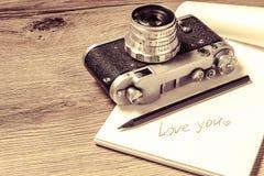 Papel con el mensaje te amo y la cámara retra Foto de archivo libre de regalías
