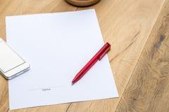 Papel con la firma y pluma roja en el escritorio Imagen de archivo