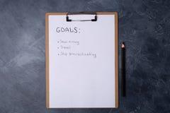 Papel con la lista de metas y de lápiz negro en la tabla gris Endecha plana Visión superior Concepto del Año Nuevo Espacio libre  fotografía de archivo