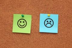Papel con las caras felices y tristes en corkboard Fotografía de archivo