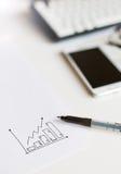 Papel cuadriculado y una pluma en la mesa Foto de archivo