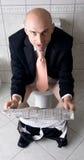 Papel da leitura do homem no toalete fotografia de stock