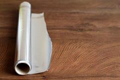 Papel de aluminio en fondo de madera Imágenes de archivo libres de regalías
