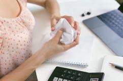 Papel de amarrotamento da mulher no local de trabalho na frente de um portátil Foto de Stock Royalty Free