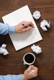 Papel de arrugamiento del hombre mientras que escribe en la libreta Fotografía de archivo libre de regalías