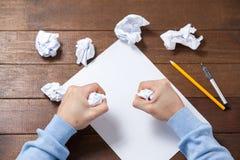 Papel de arrugamiento del hombre mientras que escribe notas Fotografía de archivo libre de regalías