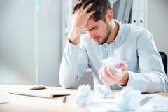 Papel de arrugamiento subrayado agotado del hombre joven en el lugar de trabajo Imágenes de archivo libres de regalías