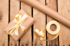 Papel de Brown que envuelve la actual mentira en superficie de madera con la cinta de oro alrededor de ella, según lo visto desde Fotos de archivo libres de regalías