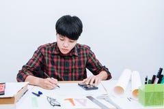 Papel de escribir en el escritorio, mano del hombre usando la calculadora que calcula el bonusOr la otra remuneración foto de archivo