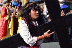 Papel de Jesus Christ que grita na dor e na agonia que levam a cruz de madeira pesada na rua fotografia de stock