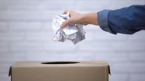 Papel de jogo da mão no escaninho de lixo, desperdício que classifica o conceito, sistema de reciclagem filme