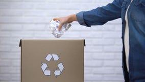 Papel de jogo da pessoa no escaninho de lixo, desperdício que classifica o conceito, sistema de reciclagem filme
