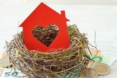 Papel de la casa con el corazón en jerarquía en el fondo del dinero - amor para el hogar, concepto casero del seguro imágenes de archivo libres de regalías
