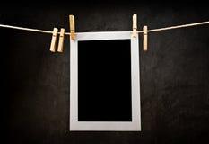 Papel de la fotografía atado a la cuerda con los pernos de ropa imagen de archivo libre de regalías