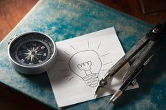 Papel de la idea con el compás en el libro Imagen de archivo