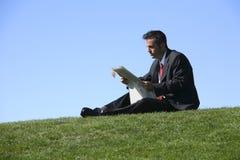 Papel de la lectura del hombre de negocios imagen de archivo