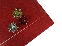 Papel de la Navidad y arqueamientos glittery rojos de las cintas foto de archivo