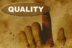 Papel de la vendimia con la mano y la palabra de la calidad Fotos de archivo