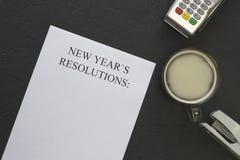 Papel de las resoluciones del ` s del Año Nuevo, una taza de café con espuma en un fondo negro Foto de archivo libre de regalías