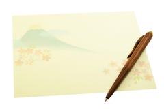 Papel de letra con la pluma de madera en el fondo blanco foto de archivo