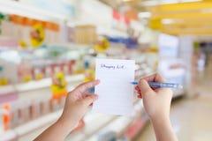 Papel de lista de compras del control de la mano con el supermercado Fotos de archivo libres de regalías