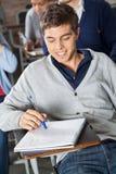 Papel de Looking At Exam do estudante na sala de aula imagem de stock