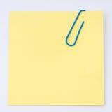 Papel de nota amarillo con el clip de papel Fotografía de archivo libre de regalías