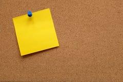 Papel de nota amarillo fijado a un tablero del corcho Imagen de archivo libre de regalías
