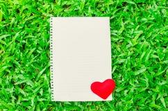 Papel de nota blanco en blanco con el corazón rojo en el fondo de cristal Fotos de archivo