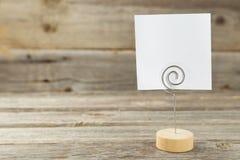 Papel de nota branco em um suporte no fundo de madeira cinzento Fotos de Stock Royalty Free