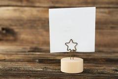 Papel de nota branco em um suporte no fundo de madeira marrom Foto de Stock Royalty Free