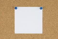 Papel de nota com os pinos do impulso na placa da cortiça Fotografia de Stock