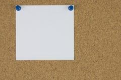 Papel de nota com os pinos do impulso na placa da cortiça Fotografia de Stock Royalty Free