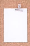 Papel de nota con el Paperclip en superficie del corcho Foto de archivo libre de regalías