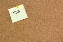 Papel de nota con feliz cumpleaños de la palabra en tablero marrón del corcho del aviso Fotos de archivo