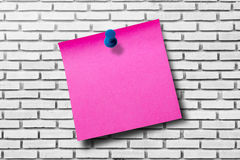 Papel de nota cor-de-rosa no fundo branco da parede de tijolo Foto de Stock Royalty Free