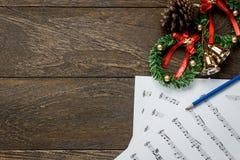 Papel de nota da música do Natal com a grinalda do Natal no wo Imagem de Stock Royalty Free