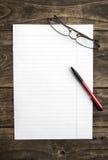 Papel de nota en blanco con la pluma en la tabla Fotos de archivo